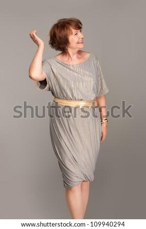 Beautiful fashionable mature woman in grey dress. Studio shot. - stock photo