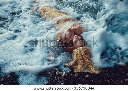 Beautiful fashionable mermaid with red hair and golden scales sitting on a rock by the sea - stock photo