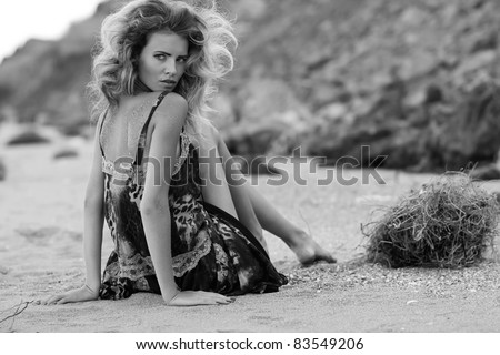 Beautiful fashionable model on the beach in beautiful dress - stock photo