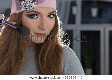 Beautiful fashionable sexy elegant girl with long hair fashionable cap on his head with an evening sitting bright makeup and painted near the mirror - stock photo