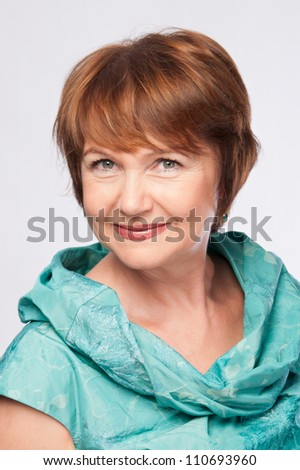 Beautiful fashionable smiling mature woman in turquoise costume head and shoulders portrait. Studio shot.