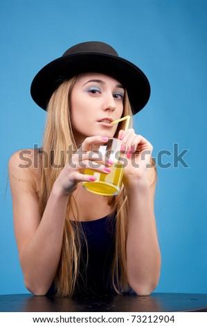 Beautiful fashionable woman drinks orange juice against blue background - stock photo