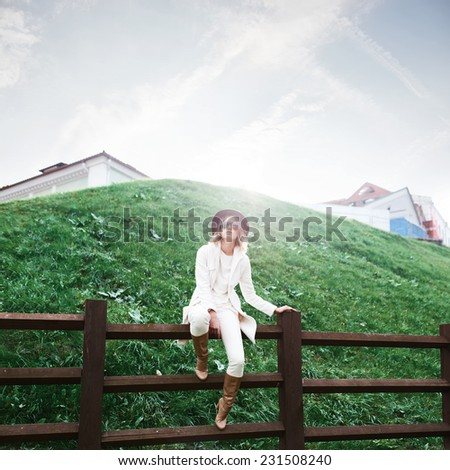 Beautiful fashionable woman in a hat and coat sitting on a fence in a sunny day - stock photo
