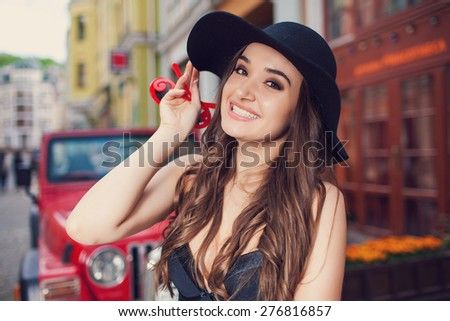 Beautiful fashionable woman in a hat and sunglasses posing over red car