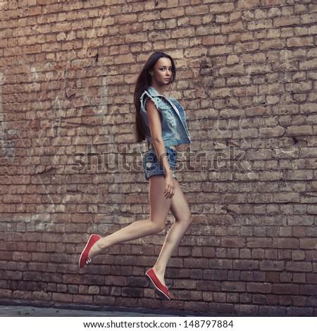Beautiful fashionable woman in a jump near the brick wall - stock photo
