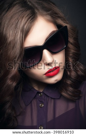 Beautiful fashionable woman in black sunglasses. Red lips. Black background. Girl in sunglasses. Toned image.