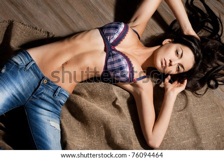 beautiful fashionable woman in bra and jeans
