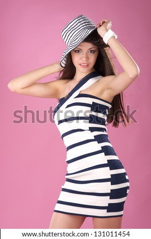 Beautiful fashionable woman in stripped hat and dress against pink background - stock photo