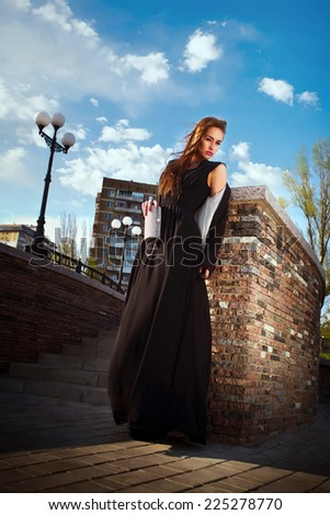 beautiful fashionable woman in the street on a sunny day - stock photo