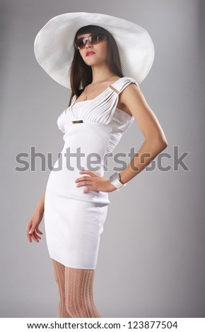 Beautiful fashionable woman in the white dress and a big hat - stock photo