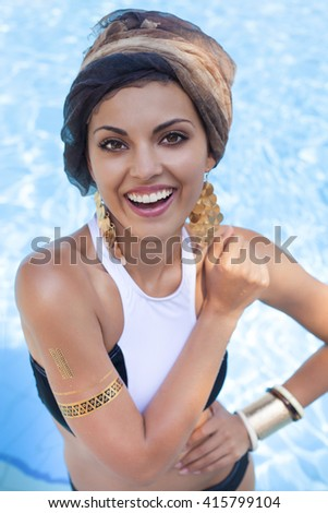 Beautiful fashionable woman near the pool wearing colored turban