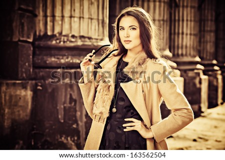 Beautiful fashionable woman standing on the city street. Sepia. - stock photo