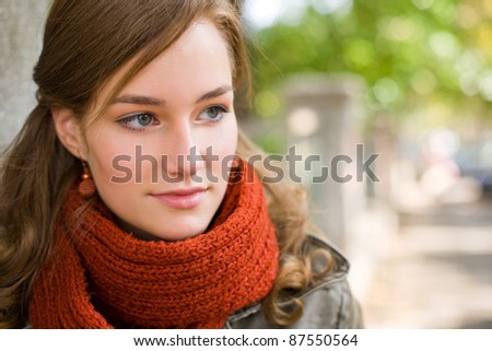 Beautiful fashionable young girl posing in the street at autumn. - stock photo