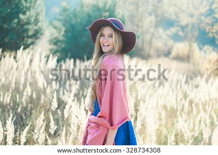 Beautiful fashionable young woman in a hat laughing in the park - stock photo