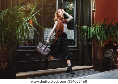 Beautiful fashionable young woman running with bag. City lifestyle. Female fashion. Full body portrait. - stock photo
