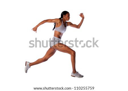 Beautiful fast running female athlete with toned muscular fitness body in grey with headset listening to music while exercising, isolated.