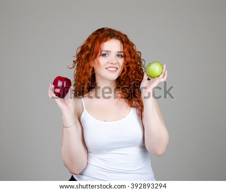 beautiful fat girl with red hair with apples in hands on grey background