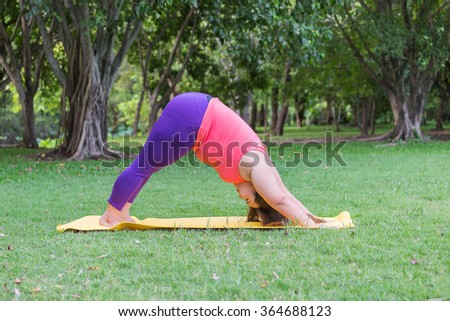 Beautiful fat woman doing yoga on the mat in the park.