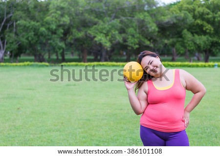 Beautiful fat woman playing dodgeball in the park. - stock photo