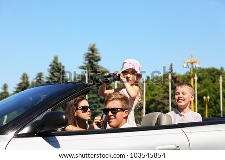 Beautiful father, mother and two children ride in convertible car and play spies - stock photo