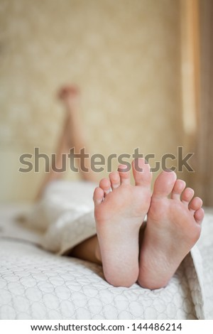 Beautiful feet of a young woman lying in bed close up