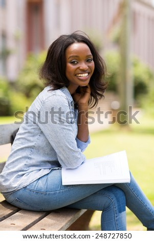 beautiful female african college student sitting in the park
