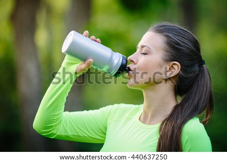 Beautiful female after running, drink water in park - stock photo