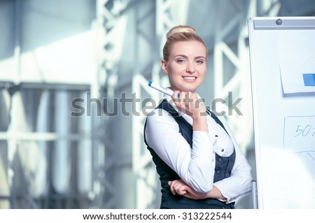 Beautiful female architect is creating sketches of building. She is standing near a board of a blueprint and holding a pencil. The woman is smiling. Copy space in left side - stock photo