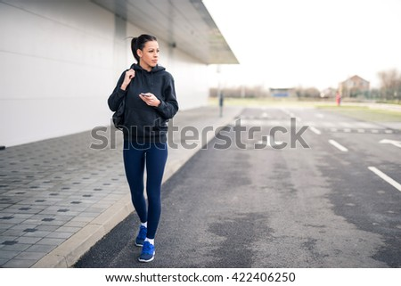 Beautiful female athlete walking in the city. - stock photo