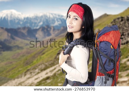 Beautiful female backpacker carrying backpack for hiking and standing on the edge of mountain while smiling on the camera