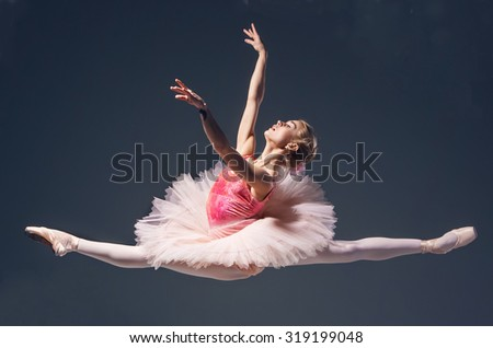 Beautiful female ballet dancer jumping on a gray background. Ballerina is wearing in  pink tutu and pointe shoes - stock photo
