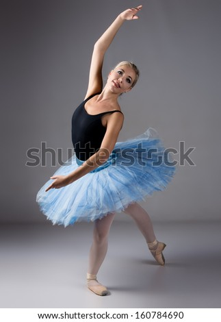 Beautiful female ballet dancer on a grey background. Ballerina is wearing a black leotard; pink stockings; pointe shoes and a blue tutu.