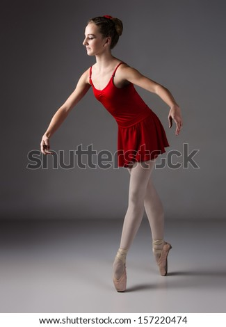 Beautiful female ballet dancer on a grey background. Ballerina is wearing a red leotard, pink stockings, pointe shoes and a red dress.