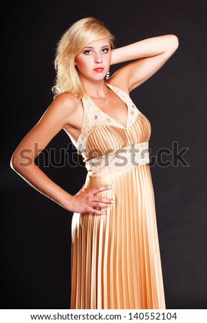 Beautiful female blonde fashion model in yellow dress black background - stock photo