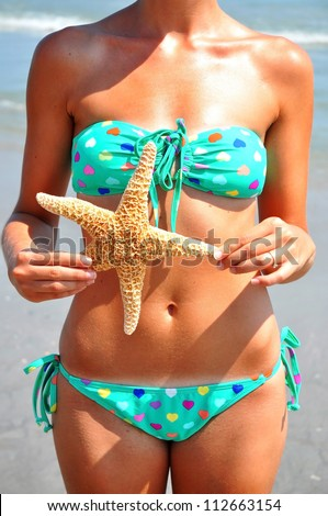 Beautiful female body holding a starfish at the ocean
