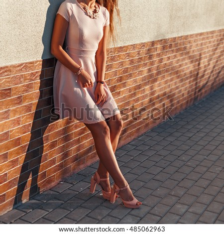 Beautiful female body in a pink dress with heels near the brick wall
