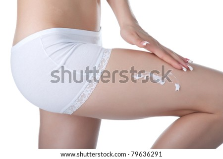 Beautiful female body isolated on white background. Sexy young woman in white panties. applying moisturizer cream on legs. Perfect female figure. Body beauty concept. - stock photo
