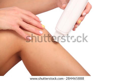 Beautiful female body legs with cosmetic container bowl and cream studio - stock photo