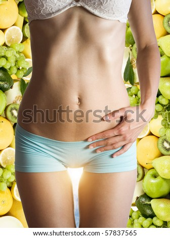 beautiful female body over fruits and sun ray