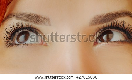 Beautiful female brown eyes with long eyelashes. Emotions. Close up of brown woman eyes looking up away, smiling, squinting and blinking. Beautiful girl eyes and eyelashes. Attractive face of female. - stock photo