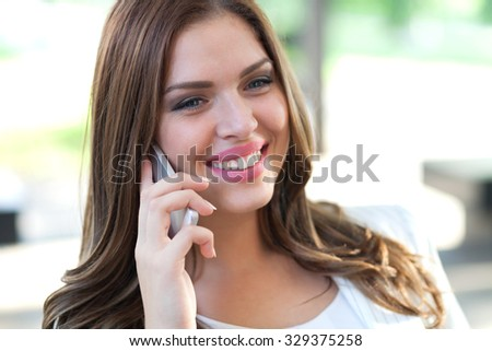 Beautiful Female Business Executive On Cell Phone In Modern City