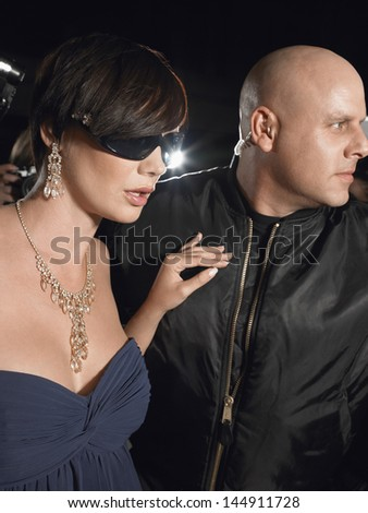 Beautiful female celebrity with bodyguard at premier - stock photo