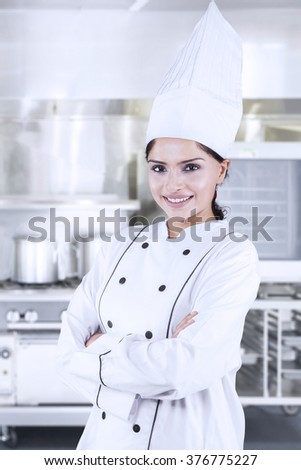 Beautiful female chef standing in the kitchen while smiling and wearing cooking wear