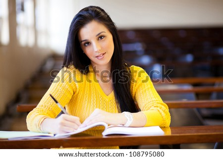 beautiful female college student sitting in lecture hall - stock photo