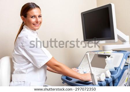 Beautiful female doctor analyzing data at hospital machine. - stock photo