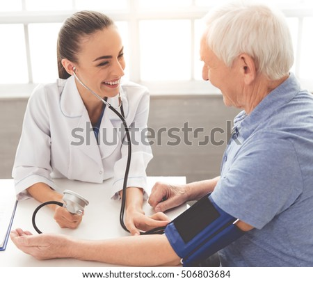 Beautiful female doctor in white medical coat is testing patient's blood pressure and smiling while sitting in office