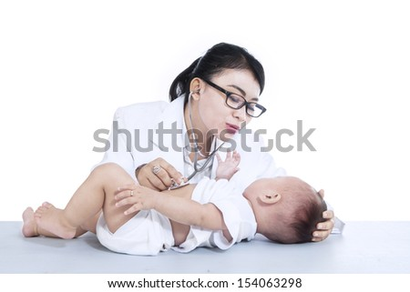 Beautiful female doctor is checking a baby with stethoscope , isolated on white - stock photo
