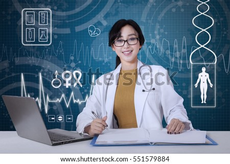Beautiful female doctor working with a laptop and document on desk, shot with virtual screen background
