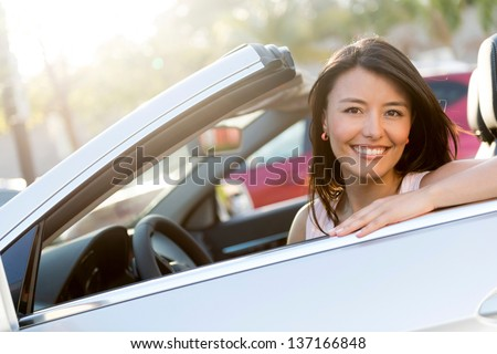 Beautiful female driver in a convertible car smiling - stock photo