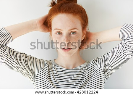 Beautiful female employee or student with red hair looking at the camera with serious and pensive expression on her face, relaxing at home during weekend. Redhead girl with clean and fresh skin - stock photo